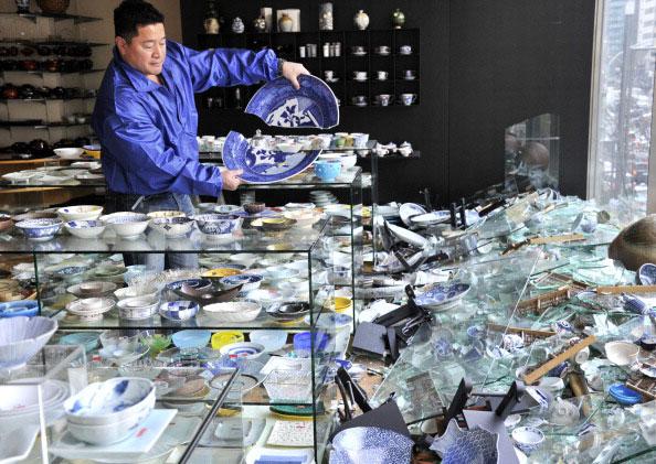 Владелец магазина керамики в Токио проверяет повреждения изделий после сильного землетрясения в Японии 11 марта 2011 года. Фото: AFP PHOTO / Yoshikazu TSUNO