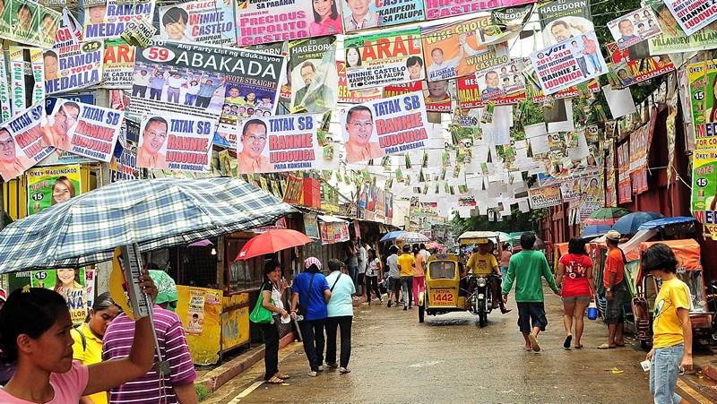 Маніла, Філіппіни, 13 травня. Мешканці гуляють вулицею, обвішаною агітаційними плакатами — країна готується до загальних проміжних виборів. Фото: Veejay Villafranca/Getty Images