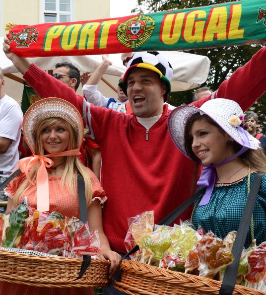 Португальський фан розмахує прапором своєї збірної, одночасно позуючи з двома українськими продавщицями цукерок 9 червня 2012 року у Львові. Фото: ANNE-CHRISTINE POUJOULAT/AFP/GettyImages
