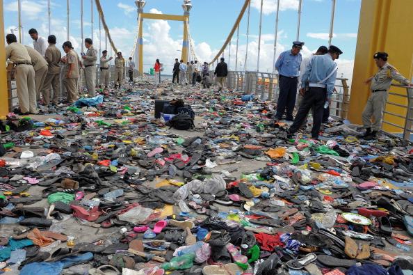 Поліцейські оглядають місце тисняви, взуття та інше сміття. Сотні скорботних камбоджійських сімей вийшли 24-25 листопада на траурну церемонію по загиблим рідним, а також висловити свій гнів з приводу неорганізованої безпеки на заході. За оцінками влади чи