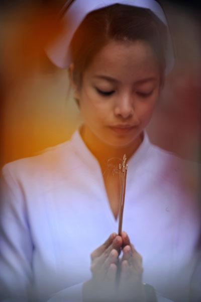 Медсестра держит в руках фимиам и молится за благополучие Короля Таиланда Пхумипхона Адульядета. Фото: CHRISTOPHE ARCHAMBAULT/AFP/Getty Images