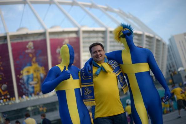 Шведські вболівальники фотографуються на тлі Олімпійського стадіону в Києві 11 червня 2012 р. Фото: Jonathan NACKSTRAND/AFP/GettyImages