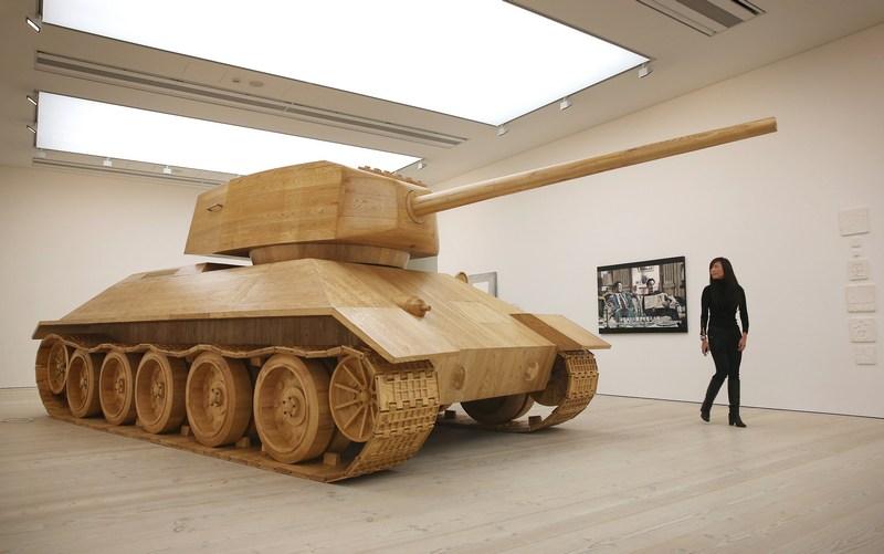 Лондон, Англія, 4грудня. Відвідувачка виставки «Погляд з Гонконгу», що проводиться в галереї Саатчі, розглядає виконану з дерева роботу «Іграшковий танк». Фото: Peter Macdiarmid/Getty Images for the Saatchi Gallery