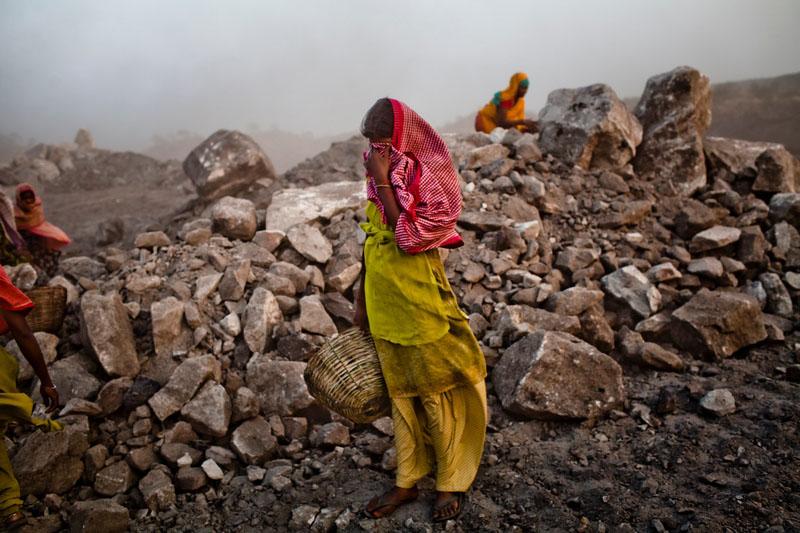 Женщины укрываются от ветра, несущего угольную пыль. Фото: Daniel Berehulak/Getty Images