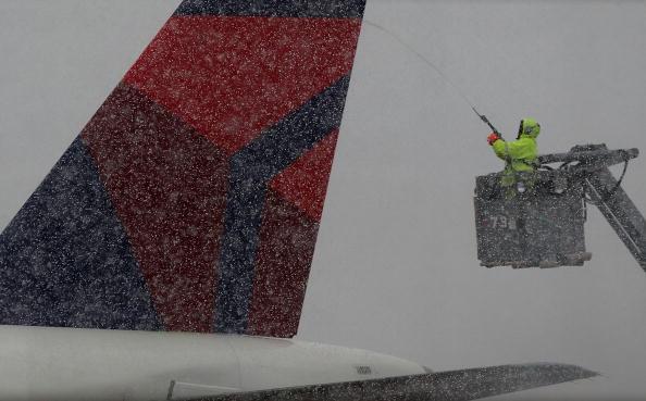 Рабочий авиалинии удаляет лед с самолета перед взлетом. Большинство полетов было отменено из-за снежных бурь. Вашингтон, 5 феварля 2010г. Фото: Mark Wilson/Getty Images