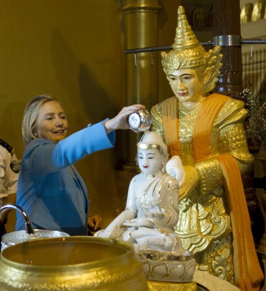 Держсекретар США Хілларі Клінтон ллє воду на статую Будди в буддійському храмі Шведагон в Янгоні. М'янма, 1 грудня 2011 року. Фото: Saul Loeb/Getty Images