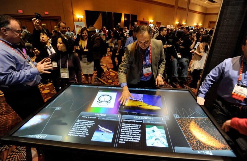Лас-Вегас, США, 6 января. Сотрудник фирмы «3М Touch Systems» Диего Ромеу представляет 84-дюймовый сенсорный стол на Международной выставке бытовой техники и электроники CES-2013. Фото: David Becker/Getty Images