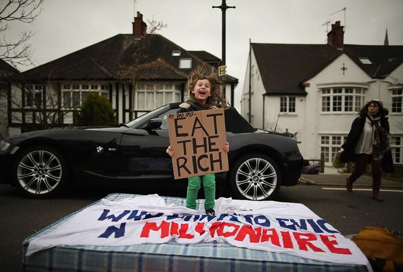 Лондон, Англия, 13 апреля. 8-летняя Люсьен протестует против решения правительства сэкономить на социальном обеспечении простых британцев. На плакате надпись: «Как говорит мой папа, ешьте богатых». Фото: Dan Kitwood/Getty Images