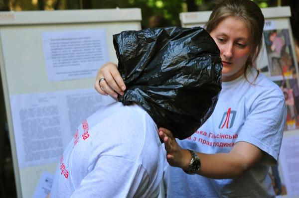 Участница акции, посвященной Международному дню против пыток, демонстрирует как в милиции душат пакетами, одевая их на голову задержанным. Фото: Владимир Бородин/The Epoch Times