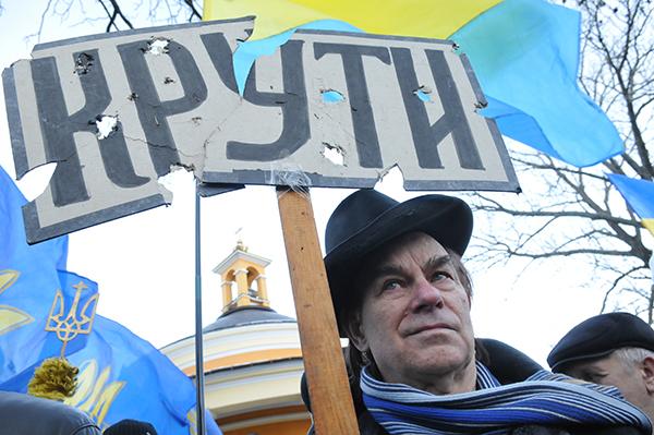Мужчина держит табличку во время памятной акции возле памятника Героев Крут на Аскольдовой могиле в Киеве 29 января 2011 года. Фото: Владимир Бородин/The Epoch Times