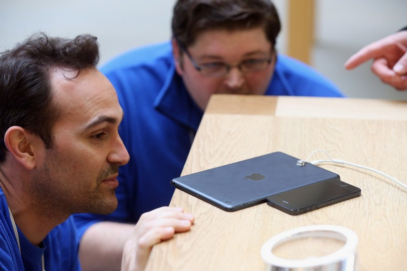 Лондон, Англия, 2 ноября. Сотрудники магазина Apple сравнивают толщину iPhone (справа) и нового планшетного компьютера «iPad mini».Фото: Oli Scarff/Getty Images