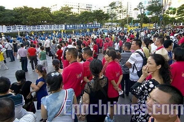 Туристи з комуністичної частини Китаю знайомляться зі змістом плакатів послідовників Фалуньгун. Фото: The Epoch Times