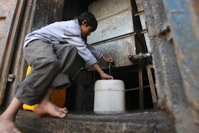 Йеменский мальчик заполняет емкость с водой из общественного крана в Сане 15 января 2012 года. Среди проблем бедной страны выделяются нехватка воды и топлива на фоне насилия и антиправительственных протестов. Фото: MOHAMMED HUWAIS / AFP / Getty Images