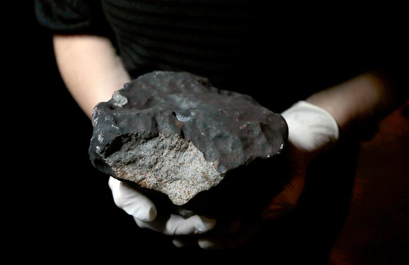 Париж, Франція, 14 червня. Співробітник Національного музею природної історії демонструє один з найбільших метеоритів вагою 5,2 кг серед тих, що впали на територію Франції. Фото: JACQUES DEMARTHON/AFP/Getty Images