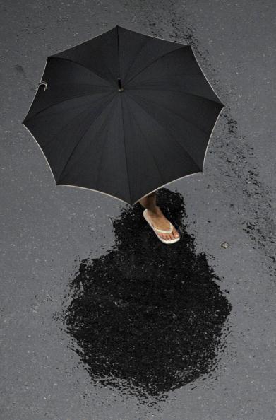 Женщина переходит улицу под проливным дождем в Буэнос-Айресе. 5 февраля 2010. Фото: JUAN MABROMATA/AFP/Getty Images