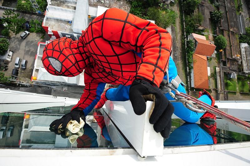 Сурабая, Индонезия, 12 июля. 37-летний мойщик окон выполняет свою работу, нарядившись в костюм человека-паука. Фото: Robertus Pudyanto/Getty Images