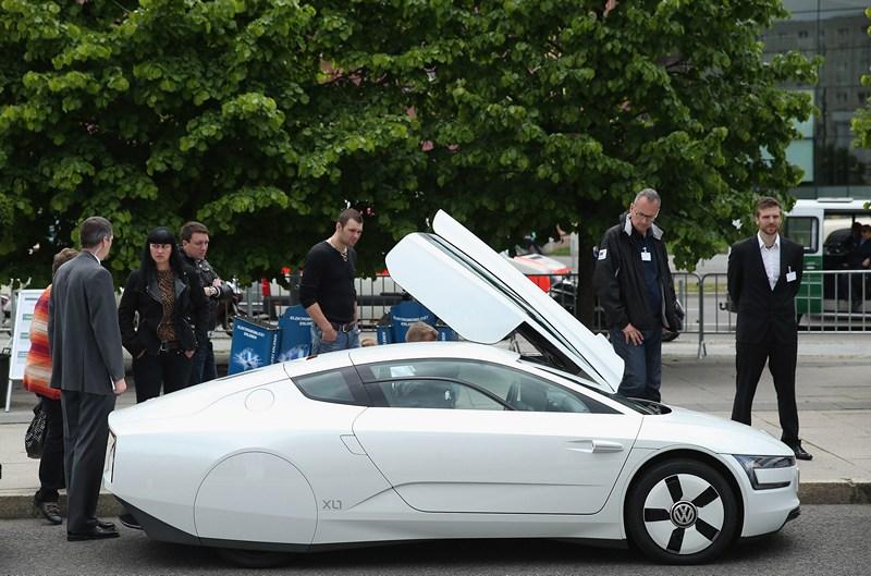 Берлін, Німеччина, 27 травня. Відвідувачі міжнародної конференції, присвяченої електромобілям, розглядають гібридний автомобіль «Фольксваген XL1». До 2020 року в країні може з'явитися до 1 млн електромобілів. Фото: Sean Gallup/Getty Images