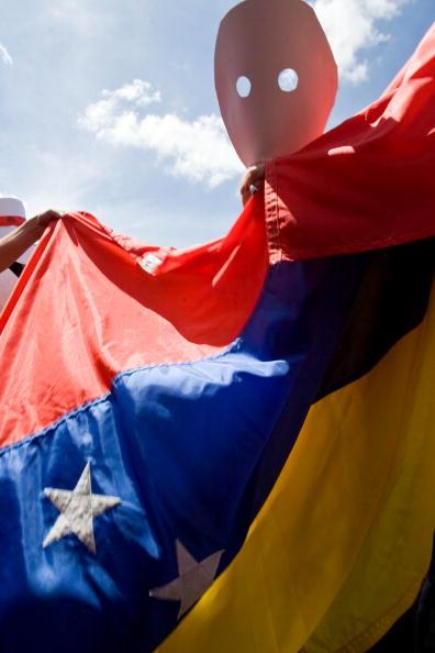 Участник акции протеста против закрытия оппозиционного канала. Каракас, Венесуэла. Фото: STR / AFP / Getty Images