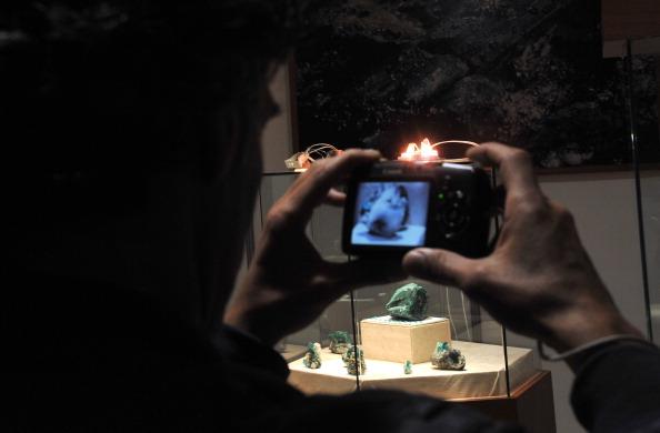 Посетитель выставки делает снимок изумруда. Фото: GUILLERMO LEGARIA/AFP/Getty Images