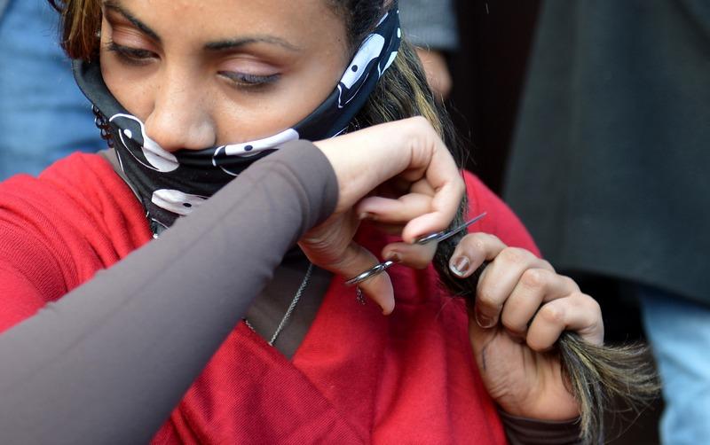 Каїр, Єгипет, 25грудня. Опозиціонерка зрізає волосся, висловлюючи протест проти утисків прав жінок, які закріплені в новій конституції країни. Фото: Khaled DESOUKI/AFP/Getty Images