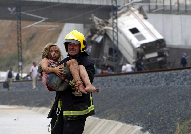 Сантьяго-де-Компостела, Испания, 24 июля. Пожарный несёт девочку, пострадавшую при аварии скоростного поезда. Фото: XOAN A. SOLER, MONICA FERREIROS/AFP/Getty Images