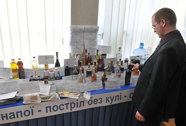 Мужчина рассматривает стол с некачественными спиртными напитками. Фото: Владимир Бородин/The Epoch Times Украина