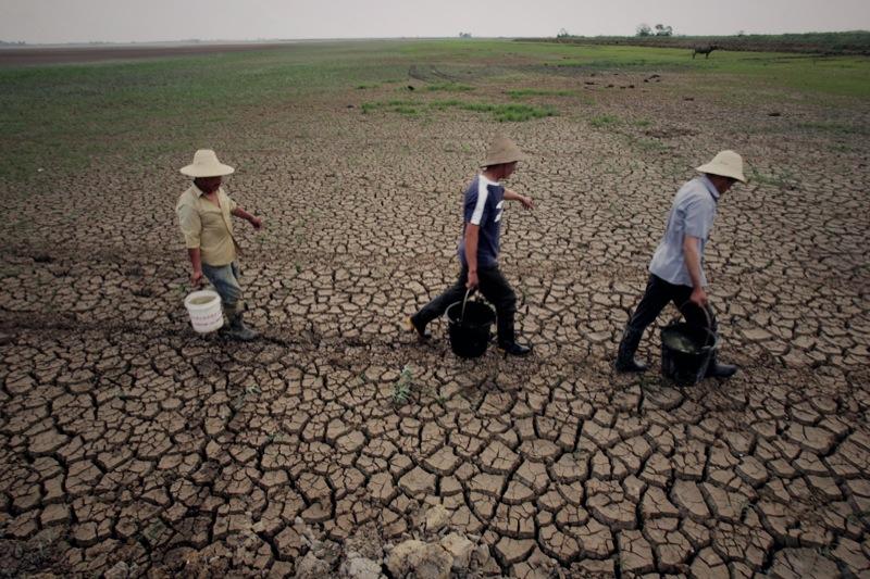 Китайские фермеры несут ведра с водой по высохшему полю в провинции Хубэй 9 мая 2011 года. Во время засухи, продолжающейся в центральном Китае в течение нескольких месяцев, более одного миллиона человек оставались без надлежащей питьевой воды. Фото: STR /