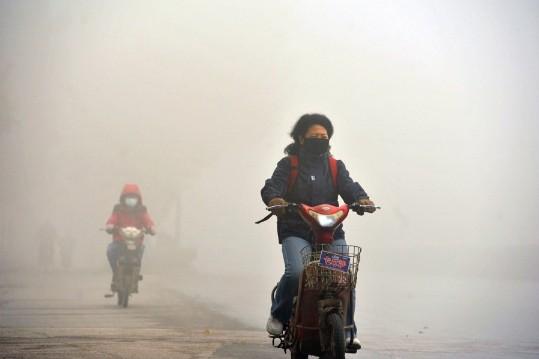 Местная жительница едет на мотоцикле с маской на лице в задымленный день. Южный Китай, Нанкин, 7 декабря. Скриншот: Netease/Велика Епоха