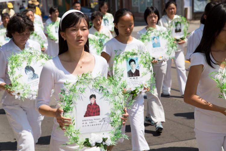 Последователи Фалуньгун несут портреты погибших единомышленников на параде в Торонто, Канада, 20 июля 2012 года. Фото: Evan Ning/The Epoch Times