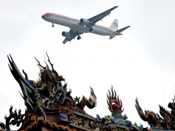 Самолёт авиакомпании China Eastern Airlines пролетает над храмом в Тайпэе, Тайвань. Фото: Patrick Lin/AFP/Getty Images